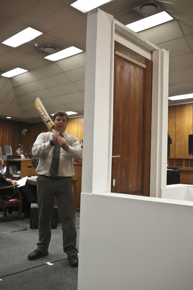 Forensic investigator Johannes Vermeulen, with cricket bat in hand, demonstrates how the toilet door could have been broken down, during the murder trial of Oscar Pistorius.