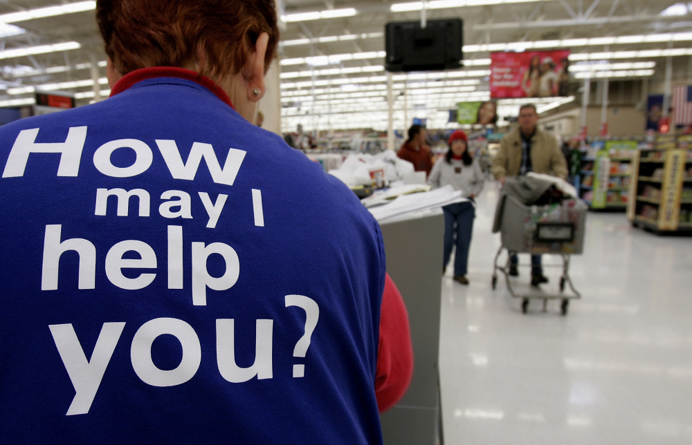 Customers at a Walmart store head to the checkout lines past a worker with the company's motto on the back of her vest, in Salt Lake City. With fewer middle-income jobs available, low-wage work is becoming a dead-end for more Walmart employees.