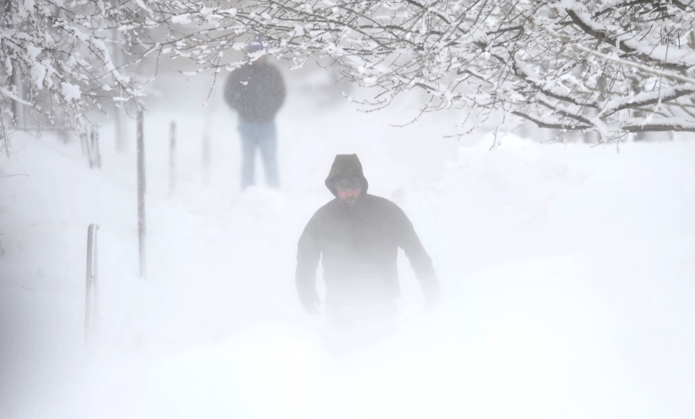 winter mist: Matt Earley clears the walkways at Colby College after a major winter storm rolled through central Maine on Thursday.