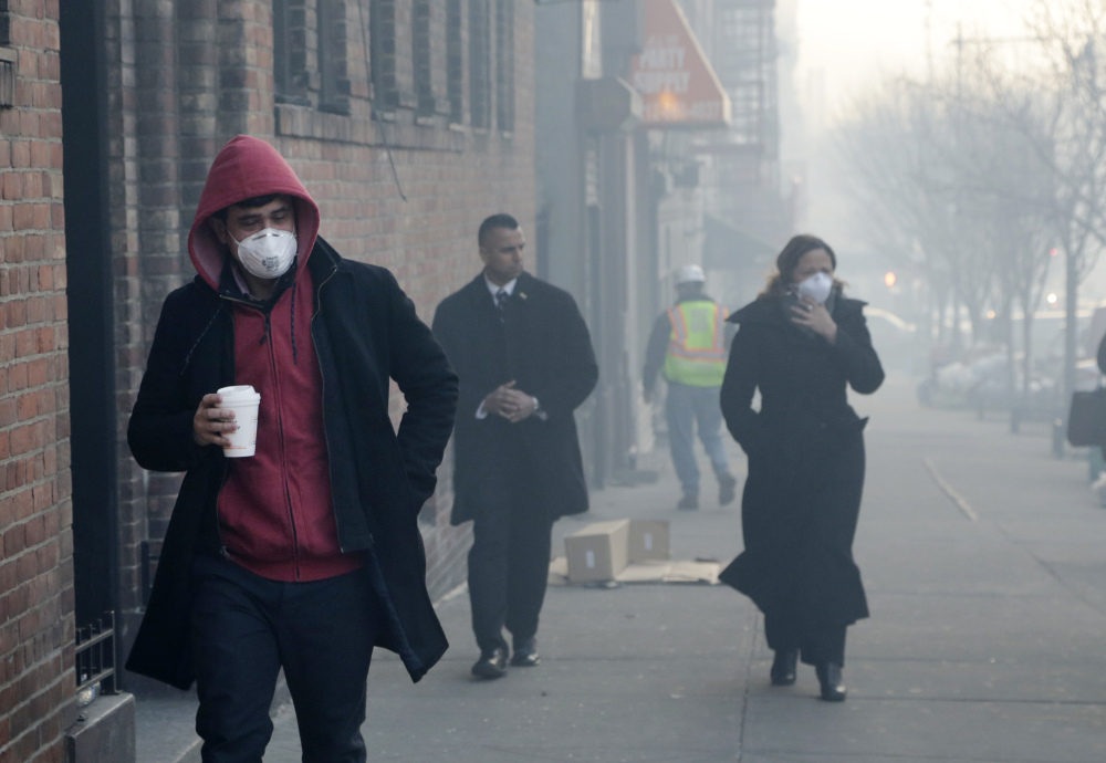 People wear dust masks as they walk near the explosion site in New York City Thursday. Rescuers working amid gusty winds, cold temperatures and billowing smoke pulled four additional bodies Thursday from the rubble of two East Harlem apartment buildings.