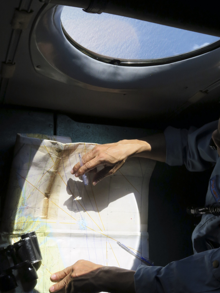 A Vietnamese Air Force crew member looks at a map during a mission Thursday over the Gulf of Thailand to search a location where Chinese satellite images showed possible debris from the missing Malaysia Airlines flight MH370.