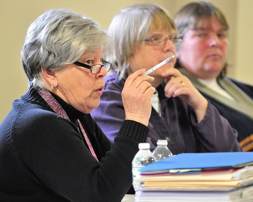 Answers: Jane Hubert, chairwoman of the Pittston Board of Selectmen, answers a question from a resident Saturday during debate at the Town Meeting in the Pittston Consolidated School. Fellow board members Vicki Kelley and Mary Jean Ambrose are at right.