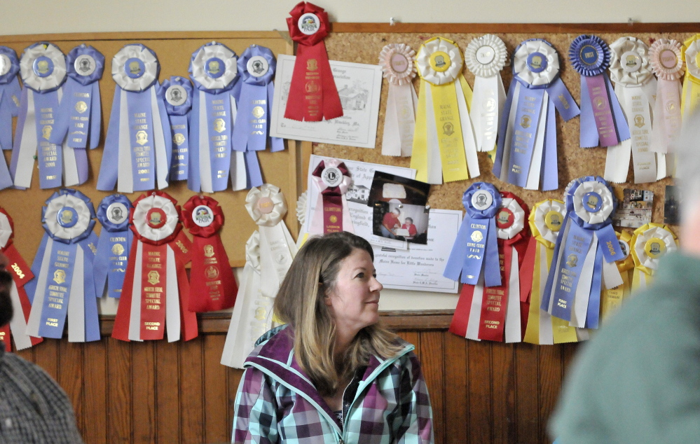 Listening: Lori Morin sits in front of a wall of ribbons Saturday while attending the Benton Town Meeting at the Benton Grange.