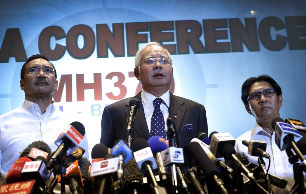 Malaysian Prime Minister Najib Razak, center, says investigators believe the missing Malaysian airliner's communications were deliberately disabled, that it turned back from its flight to Beijing, and that it flew for more than seven hours.