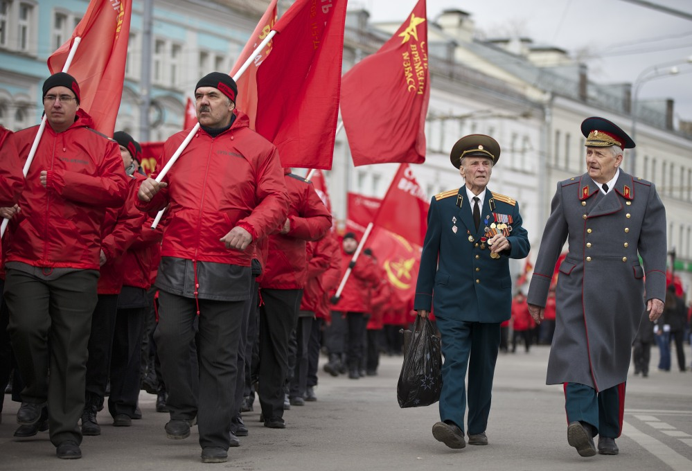 Demonstrators wearing red and two WWII veterans, right, march in support of Kremlin-backed plans for the Ukrainian province of Crimea to break away and merge with Russia, in Moscow on Saturday.
