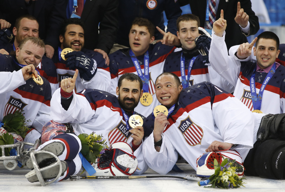 The Associated Press United States players pose for a team photo after winning the gold medal after their ice sledge hockey match against Russia at the 2014 Winter Paralympics in Sochi, Russia, on Saturday. The United States won 1-0 to defend its title.