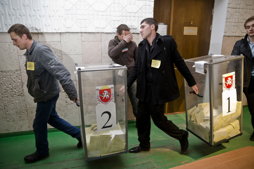 Referendum officials carry ballot boxes at a polling station after voting ended in Simferopol, Ukraine, Sunday, March 16, 2014. Polls have closed in Crimea's contentious referendum on seceding from Ukraine and seeking annexation by Russia.
