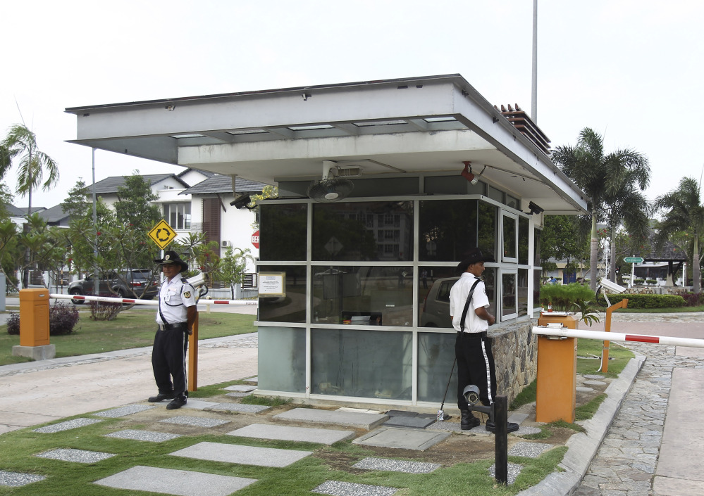 Security guards stand at a main gate of missing Malaysia Airlines pilot Zaharie Ahmad Shah's house in Shah Alam, outside Kuala Lumpur on Saturday. Malaysian police have already said they are looking at the psychological state, the family life and connections of pilot Zaharie, 53, and co-pilot Fariq Abdul Hamid, 27. Both have been described as respectable, community-minded men.