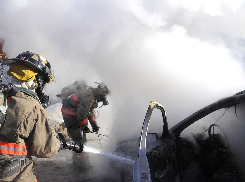 BURN-OUT: Hallowell firefighter Lt. Peter Schumacher, right, pries open the hood of a car on fire Monday as his colleague, Richard Seymour, hoses down the dashboard in the parking lot of the Lucky Garden Restaurant in Hallowell. The blaze destroyed the Ford station wagon, but no injuries were reported, firefighters said.