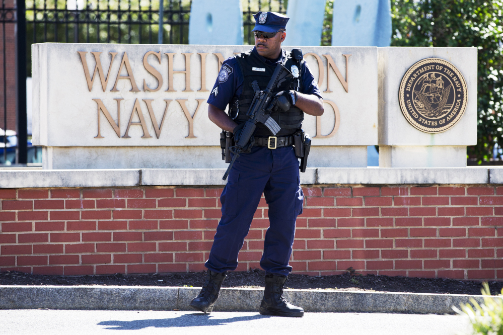 This Sept. 17, 2013 file photo shows an armed officer who said he is with the Defense Department, standing near guard the gate at the Washington Navy Yard the day after a gunman launched an attack inside the Yard.