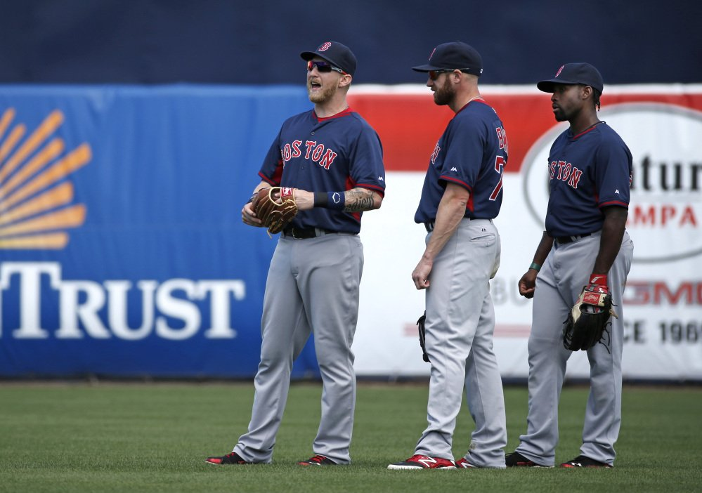 Boston Red Sox left fielder Mike Carp, left, calls to an umpire explaining that a swarm of bees have taken over left, field in the bottom of the third inning as Red Sox right fielder Corey Brown, center, and center fielder Jackie Bradley Jr. watch during a spring exhibition baseball game against the New York Yankees in Tampa, Fla., Tuesday, March 18, 2014. The game was delayed seven minutes as groundskeepers eradicated the swarm with insecticide.