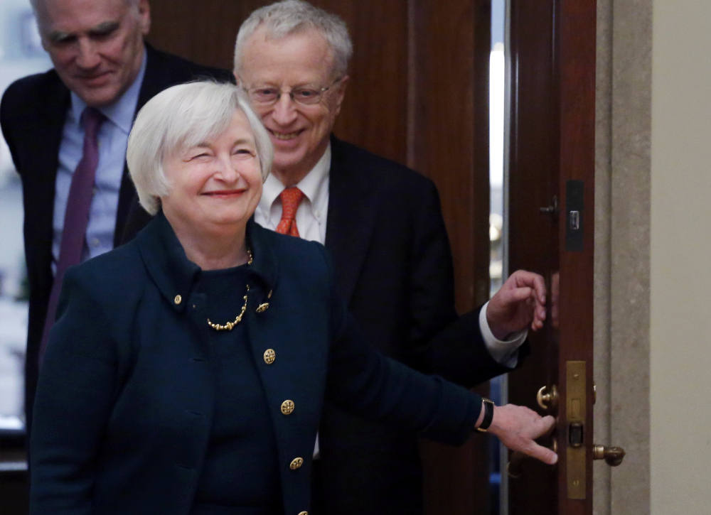 In this Monday, Feb. 3, 2014, file photo, Janet Yellen, followed by her husband, Nobel Prize winning economist George Akerlof, smiles as she walks into a room of applause by staff members before she is administered the oath of office as Federal Reserve Board chair, at the Federal Reserve in Washington.