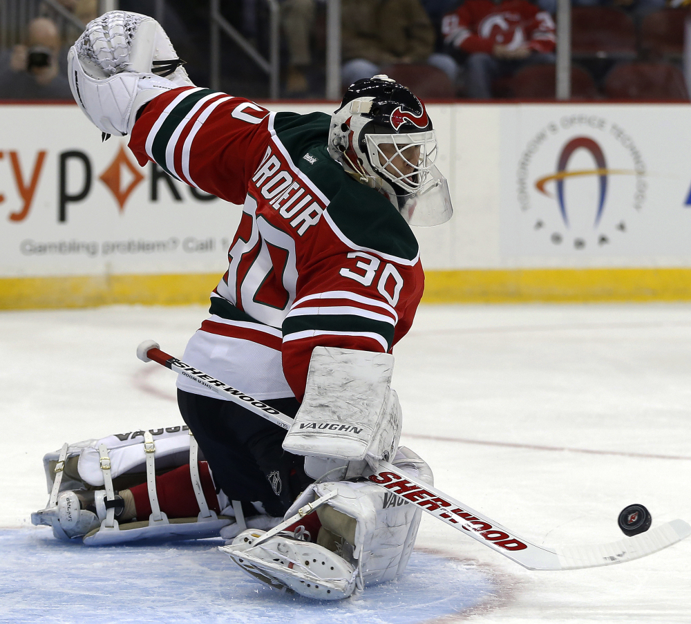 New Jersey Devils goalie Martin Brodeur makes a save on a shot by the Boston Bruins during the first period of an NHL hockey game, Tuesday, March 18, 2014, in Newark, N.J.