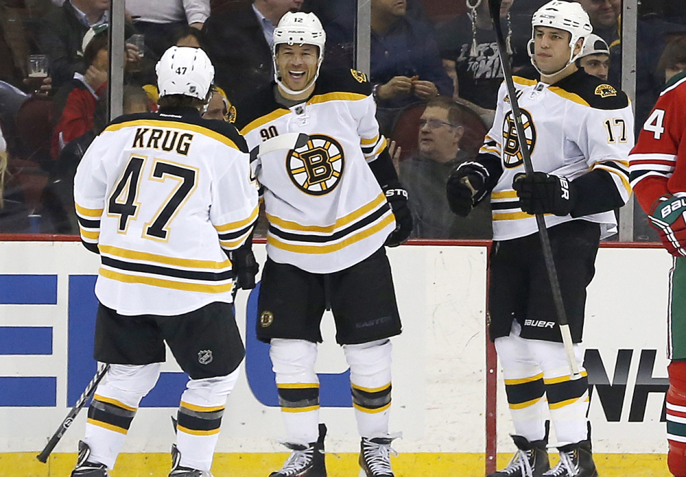 Boston's Torey Krug, left, Jarome Iginla, center, and Milan Lucic celebrate Iginla's goal during a 4-2 win by the Bruins on Tuesday against the New Jersey Devils at Newark, N.J.