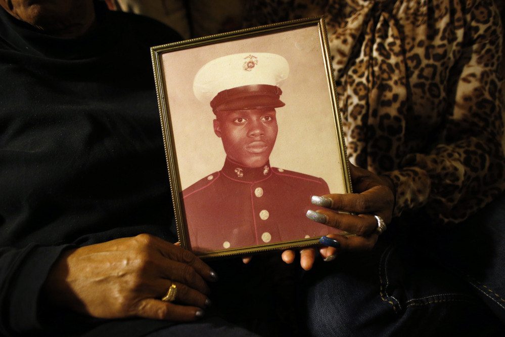 In this March 12, 2014 photo, a picture of Jerome Murdough is held by his mother Alma Murdough left, and sister Cheryl Warner at Alma Murdough's home in the Queens borough of New York.