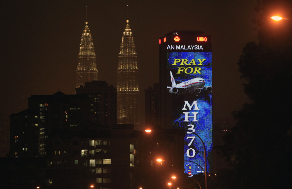 """An office building is illuminated with LED lights displaying """"Pray for MH370"""" next to Malaysia's landmark Petronas Twin Towers in Kuala Lumpur, Malaysia, Wednesday, March 19, 2014. Investigators are trying to restore files deleted last month from the home flight simulator of the pilot aboard the missing Malaysian plane to see if they shed any light on the disappearance, Malaysia's defense minister said Wednesday."""