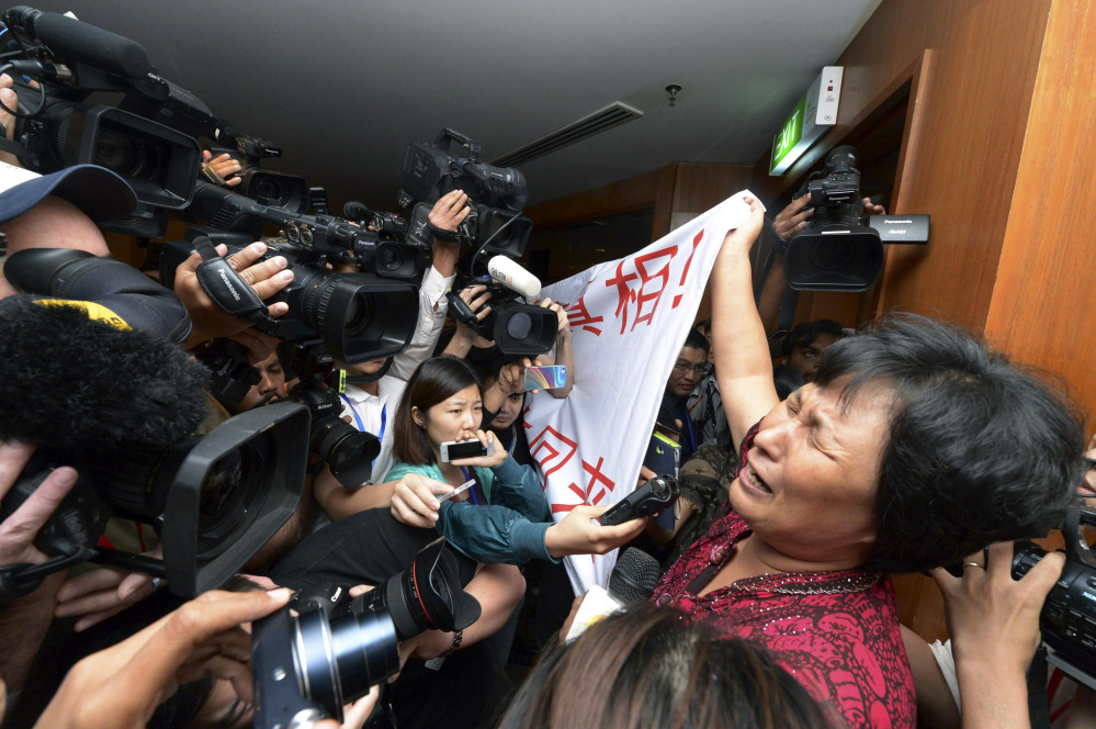 "A Chinese relative of passengers aboard a missing Malaysia Airlines plane cries as she holds a banner in front of journalists reading 'We are against the Malaysian government for hiding the truth and delaying the rescue. Release our families unconditionally!"" at a hotel in Sepang, Malaysia, Wednesday, March 19, 2014. Malaysian authorities examined new radar data from Thailand that could potentially give clues on how to retrace the course of the Malaysia Airlines plane that vanished early March 8 with 239 people aboard en route from Kuala Lumpur to Beijing. Twenty-six countries are looking for the aircraft as relatives anxiously await news."