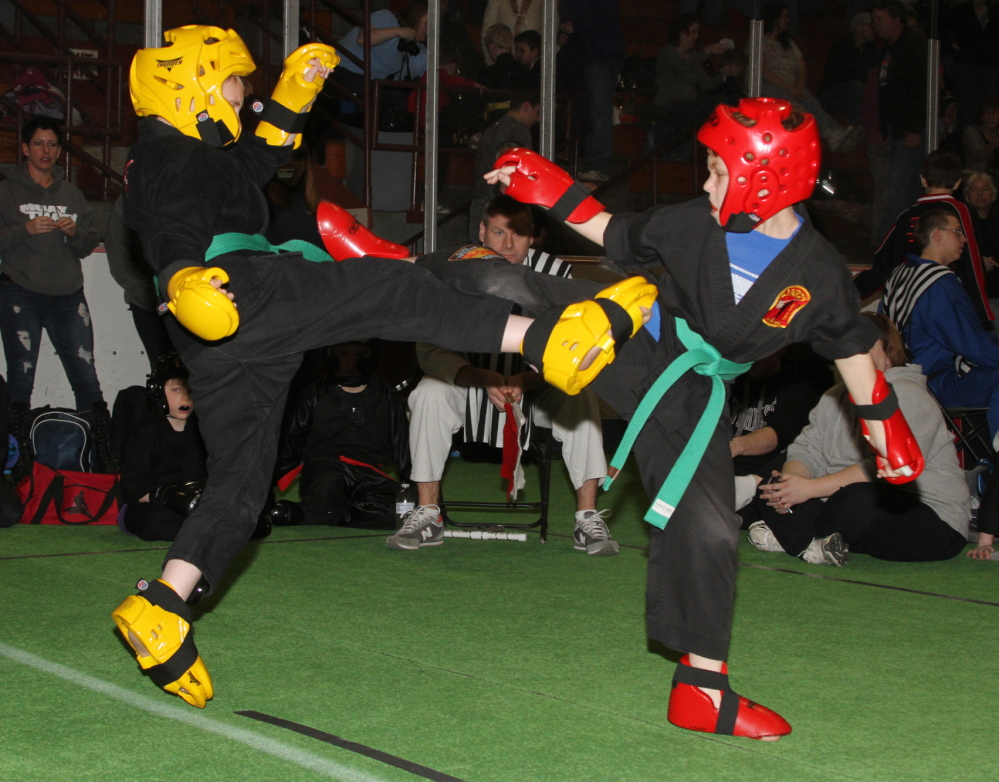GETTING READY: Huard's Martial Arts students Zachary Bean, 11, of Sidney point fights with Cameron Audet, 12, of Winslow during the 2013 Battle of Maine Martial Arts Championships. Hundreds of martial artists from around New England and Canada will be competing in this weekend's Battle at Sukee Arena in Winslow on Saturday from 10 a.m. to 5 p.m.