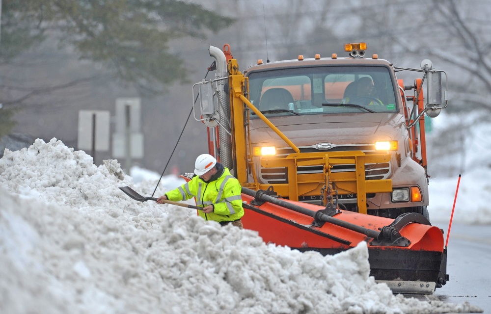 Staff photo by Michael G. Seamans SPRING STORM: Drew Veilleux, with the Maine DOT shovels snow from the side of the road with his plow waiting behind him on US Route 201 in Hinkley on Thursday. Crews are working to clear snow and slush from the side of the roads to help drainage issues.