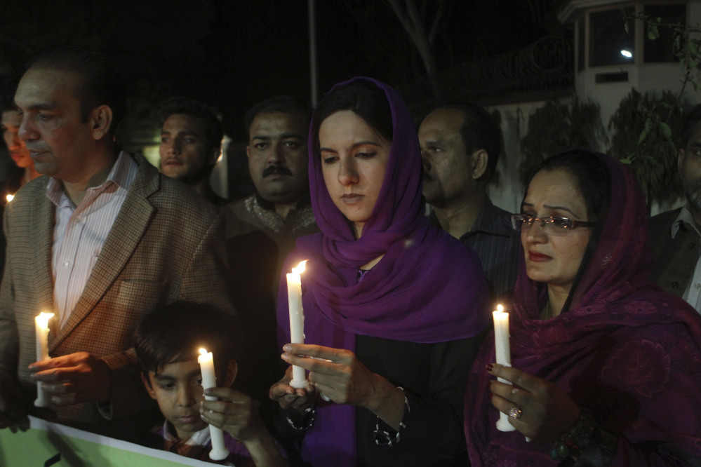 """Pakistanis hold candles for the passengers of a Malaysia Airlines plane that disappeared on March 8, while holding a candlelight vigil organized by Peace for Life Welfare Foundation in Lahore, Pakistan, on Thursday. An air search in the southern Indian Ocean for possible objects from the missing Malaysia Airlines plane described as the """"best lead"""" so far ended for the day without success Thursday but will resume in the morning, Australian rescue officials said."""