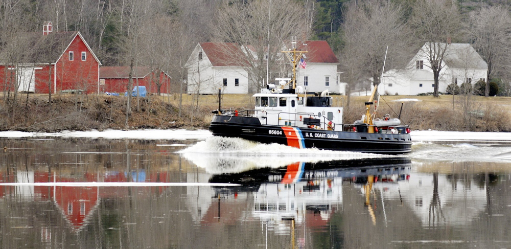 breaking the ice: In this 2012 file photo, a Coast Guard ice cutter cruises up the Kennebec River past the Moulton Farm in Pittston. This year, the cutters will hit a lot more ice on the river.