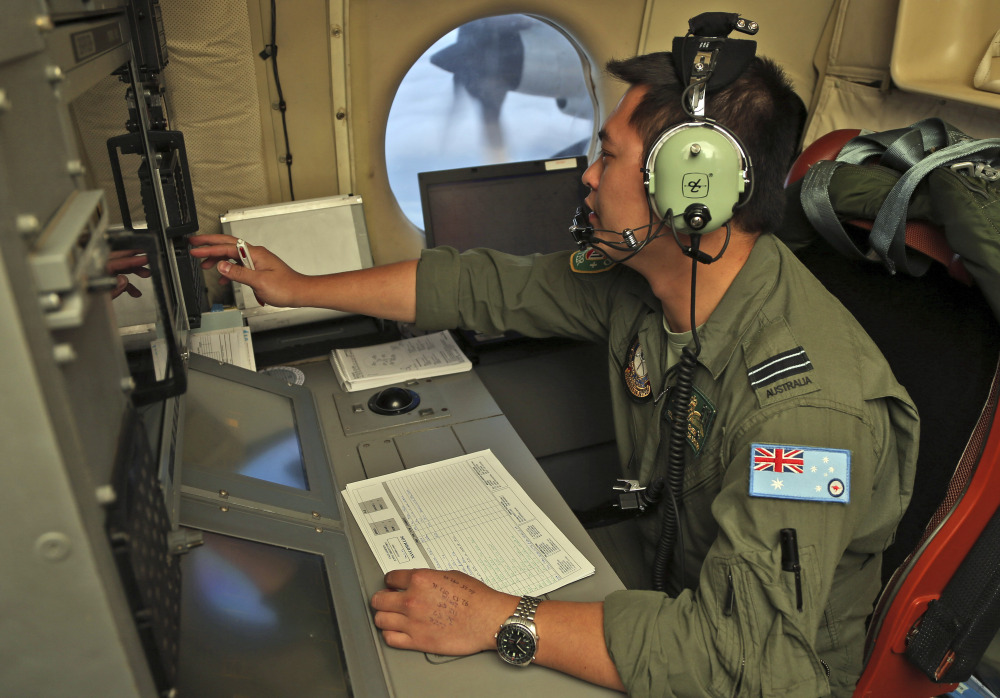 Flight Officer Jack Chen mans the navigation and communication station on board a Royal Australian Air Force AP-3C Orion as they search for missing Malaysia Airlines flight MH370 in southern Indian Ocean, Australia, on Saturday.