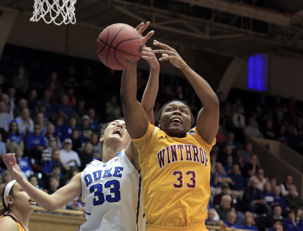 Duke's Haley Peters, left, fights for a rebound with Winthrop's Erica Williams during the first half of their first-round game in the NCAA basketball tournament in Durham, N.C., on Saturday.