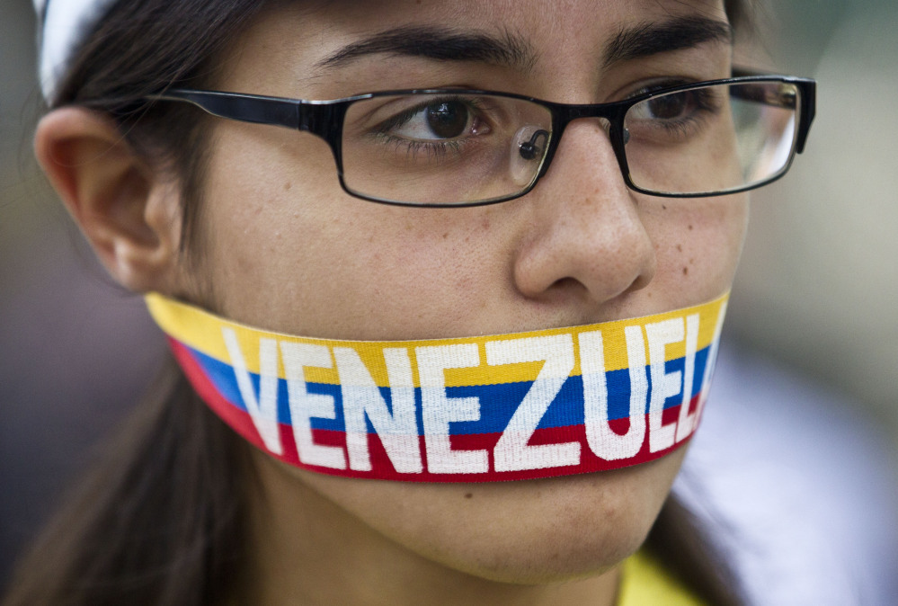 """An anti-government demonstrator stands with a tri-colored ribbon covering her mouth that reads """"Venezuela"""" during a protest in front of an office of the Organization of American States, OAS, in Caracas, Venezuela, on Friday."""