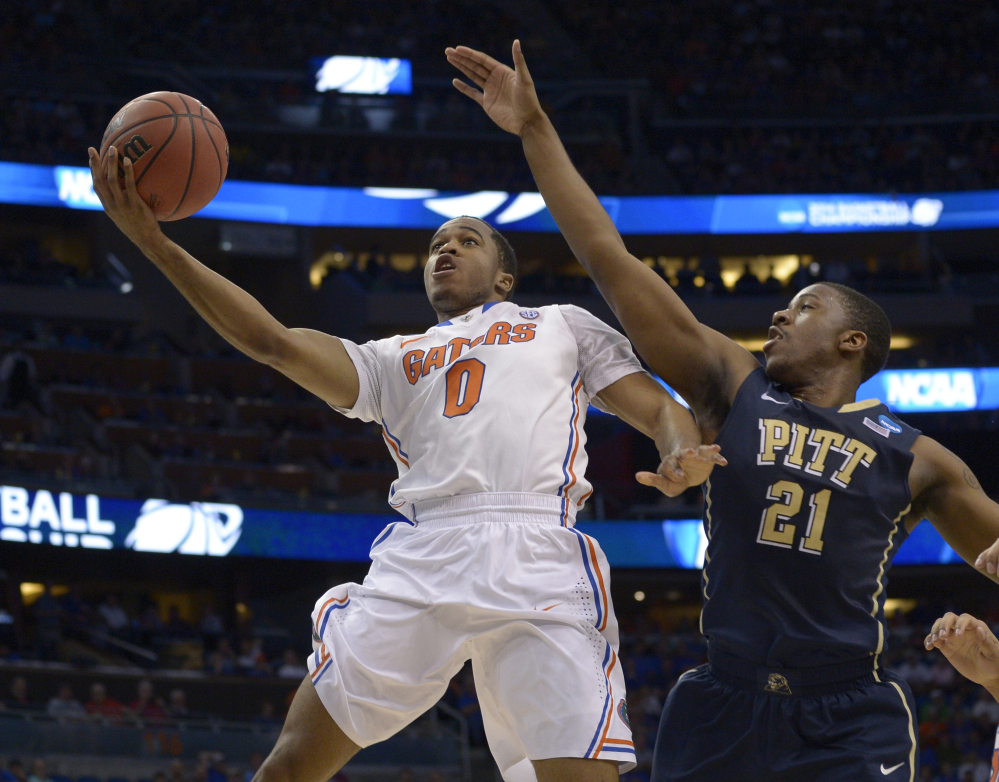 Florida guard Kasey Hill, 0 , drives to the basket as Pittsburgh forward Lamar Patterson defends during the first half of Saturday's third-round game in the NCAA tournament Saturday at Orlando, Fla. The Gators won, 61-45.