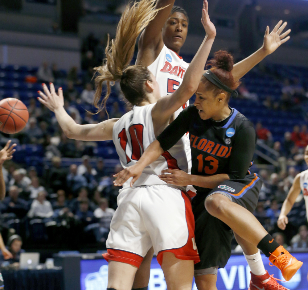 Florida's Cassie Peoples, right, passes around Dayton's Andrijana Cvitkovic and in front of Celeste Edwards.