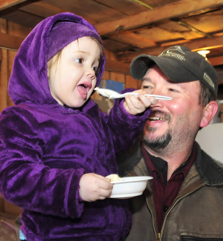 YUMMY: Wayne Smith holds his granddaughter Haleigh Hutchins as she enjoys some ice cream topped with maple syrup during a Maine Maple Sunday event at the Rodney Hall farm in East Dixfield on Sunday.