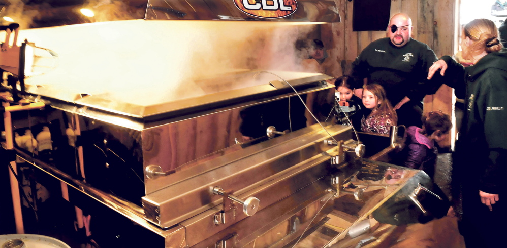 SWEET: Beside a working evaporator, Joe Gould speaks with visitors who stopped in to learn about maple syrup process during a Maine Maple Sunday event at Sunrise Maple farm in East Dixfield on Sunday.