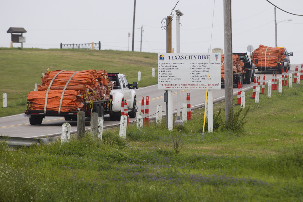 Environmental personnel drive onto the Texas City Dike with oil containment booms for oil remediation following a barge collision in the ship channel, causing an oil spill on Saturday. The barge carried 924,000 gallons of fuel oil.