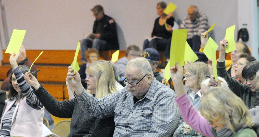 Voting: Residents hold up green cards to cast votes during Washington's Town Meeting on Saturday in Prescott Memorial School in Washington.