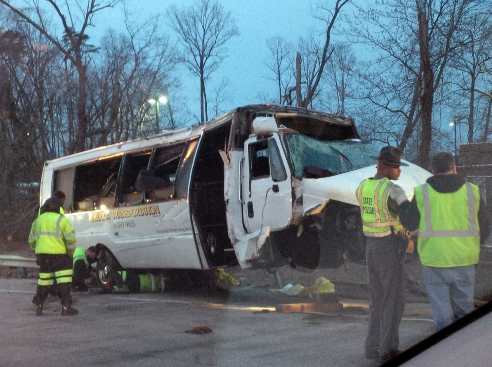 Police investigate the scene of a bus accident on Interstate 95, early Sunday in Fairfax County, Va. The shuttle bus struck a guardrail and overturned before dawn Sunday just south of the nation's capital, leaving at least one person dead and sending 16 others to the hospital, Virginia State Police said.