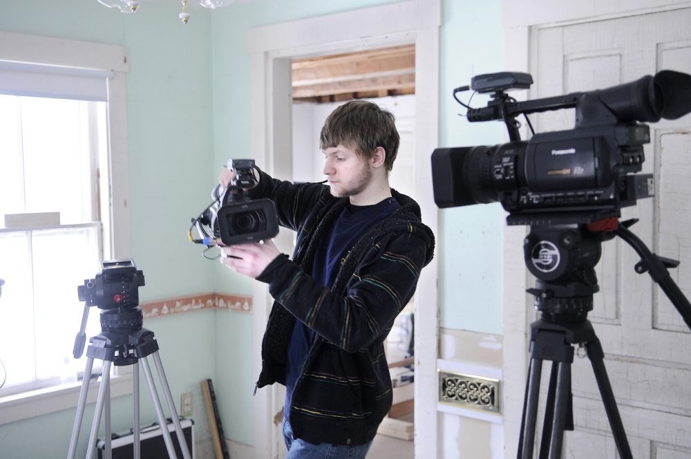 FINE HOMES: Erskine Academy senior Matt Plourde sets up video cameras Wednesday for a piece that Fine Homebuilding magazine is recording at a home in Palermo. A crew of three from the Connecticut magazine is working for a week at the 19th century cape that carpenter Mike Maines is renovating. Plourde, of Winslow, is assisting the crew.