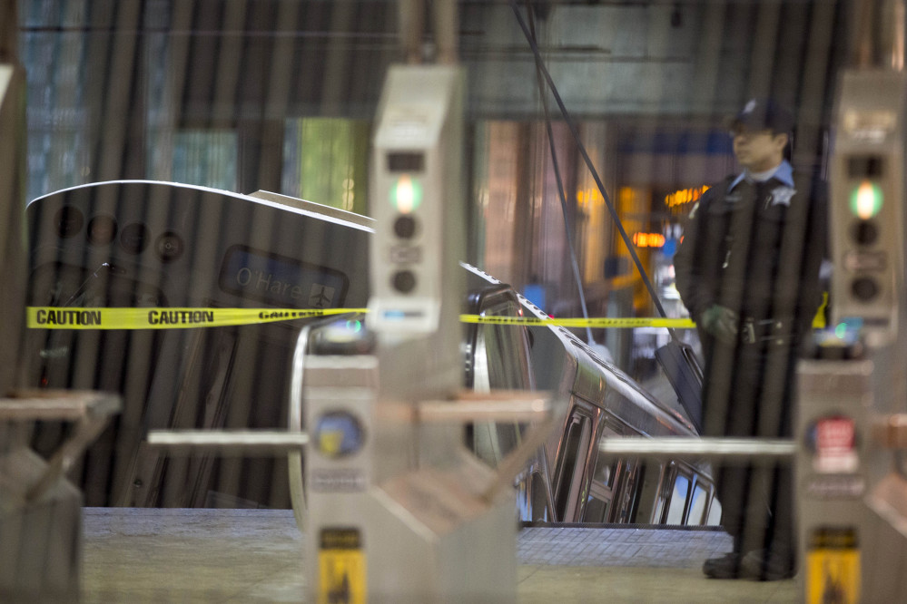 A police officer stands near a Chicago Transit Authority train car that derailed at the O'Hare Airport station early Monday.