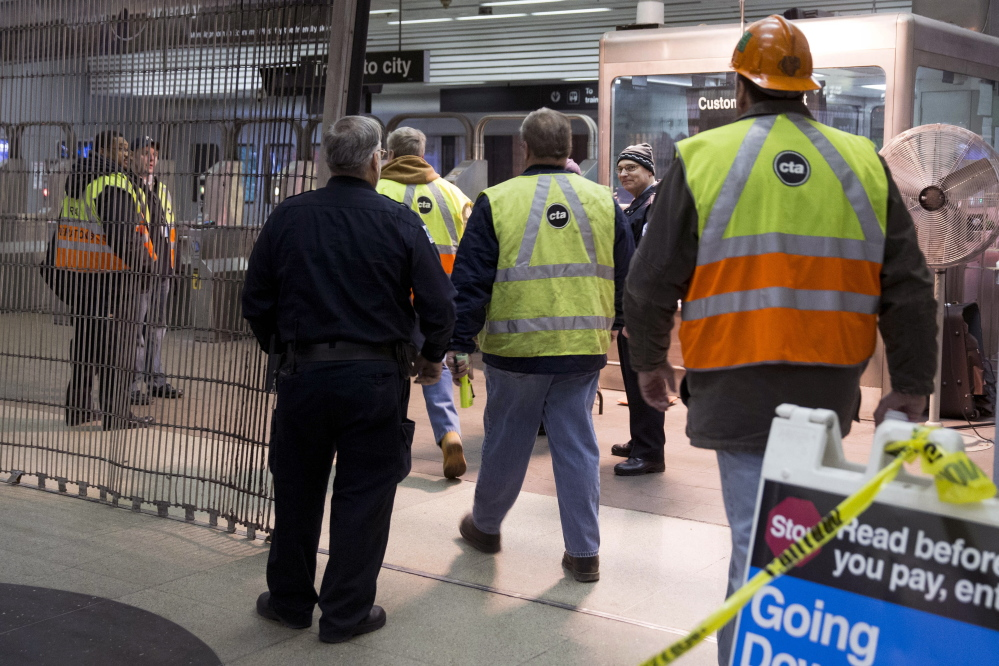 Chicago Transit Authority employees work the scene where a Chicago Transit Authority derailed at the O'Hare Airport station early Monday. More than 30 people were injured after the eight-car train plowed across a platform and scaled an escalator at the underground station.