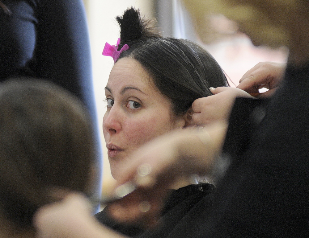 GIVING BACK: Renee Grant, center, of Gardiner gets a new look Monday after donating her hair to Locks of Love, a charity that gives hair to children, during an event at the University of Maine at Augusta. Students from Capilo Institute of Augusta donated their services to cut the hair.