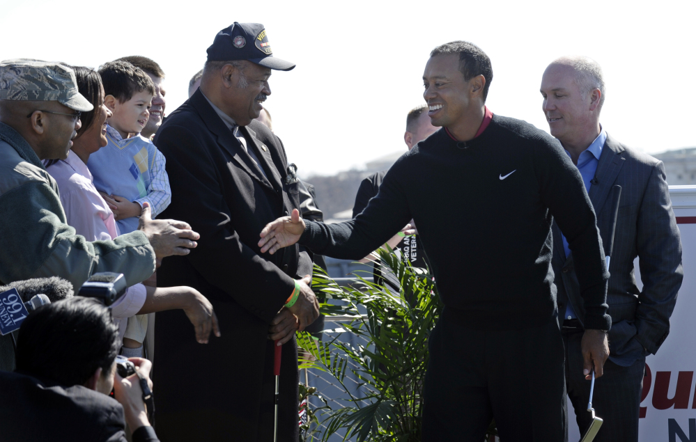 Tiger Woods, second from right, shakes hands following a putting challenge at the Newseum in Washington, Monday.