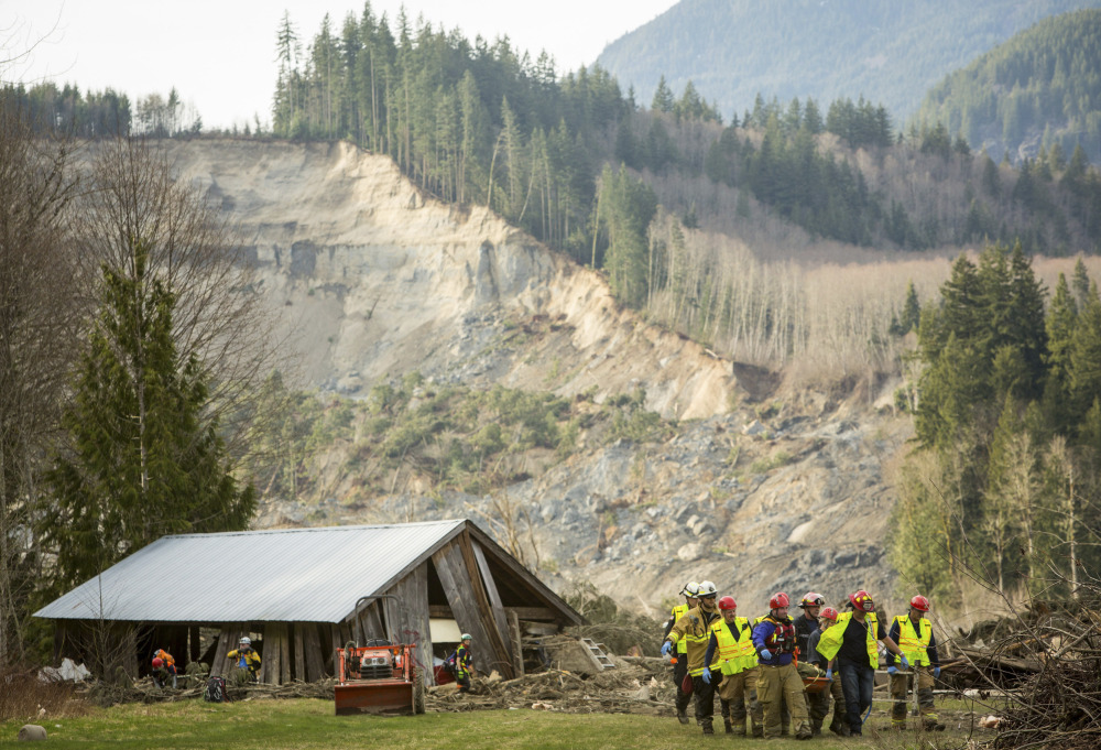 Rescue workers remove one of a number of bodies from the wreckage of homes destroyed by a mudslide near Oso, Wash., Monday.