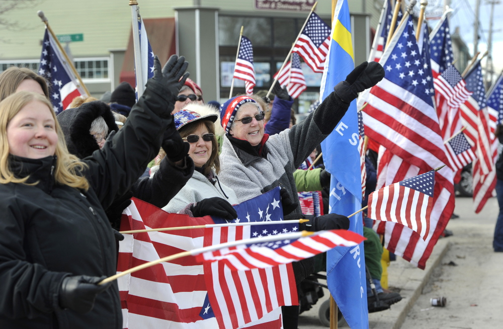 Cathy Cunningham, in the center of the photo, raises a mitten-covered hand in salute as she and dozens of other supporters wave at passing vehicles in support of the Freeport Flag Ladies, including Carmen Footer, who is recovering from heart surgery and missed the weekly ritual.