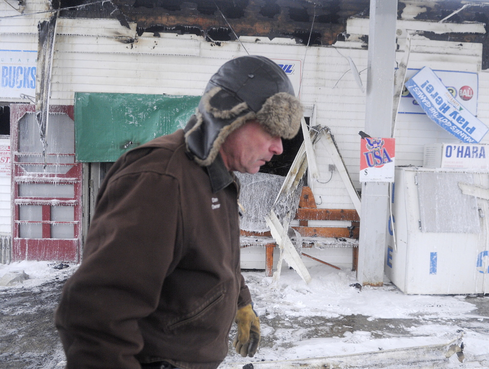 AFTERMATH: Webb's Store owner Dan Kilmer walks past the burned business Wednesday morning after an early morning fire. Kilmer said his security firm called him at 3 am to report an alarm and when he arrived minutes later, the building was engulfed in smoke.