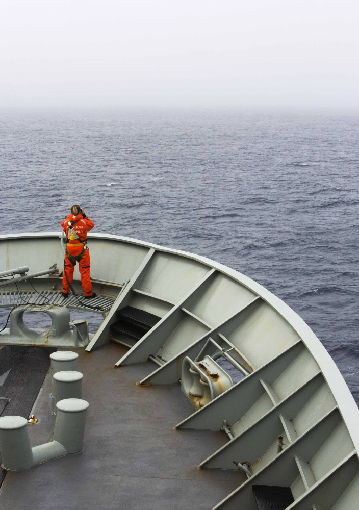 A lookout is stationed on the bow of HMAS Success during the search in the southern Indian Ocean for signs of missing Malaysia Airlines Flight MH370. The desperate, multinational hunt resumed Wednesday across a remote stretch of the Indian Ocean after fierce winds and high waves that had forced a daylong halt eased considerably.