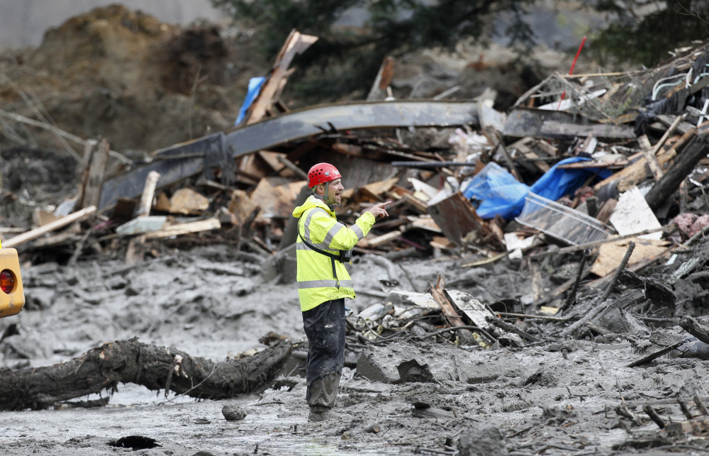A searcher stands among debris at the scene of the deadly mudslide in Oso, Wash., on Wednesday. The debris field is about a square mile and, in places, 30 to 40 feet deep.