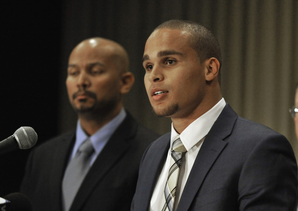 Northwestern quarterback Kain Colter, right, speaks while College Athletes Players Association President Ramogi Huma listens during a news conference in Chicago in January. In a landmark ruling, a federal agency on Wednesday gave football players at Northwestern University the green light to unionize.