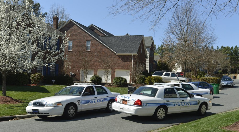 Charlotte-Mecklenburg Police Department cars sit outside Charlotte Mayor Patrick Cannon's home as federal agents search the house on Wednesday.