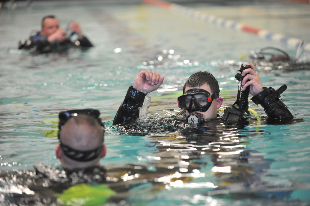 Masked men: Dive team members cluster in the pool at the Alfond Youth Center in Waterville on Tuesday.