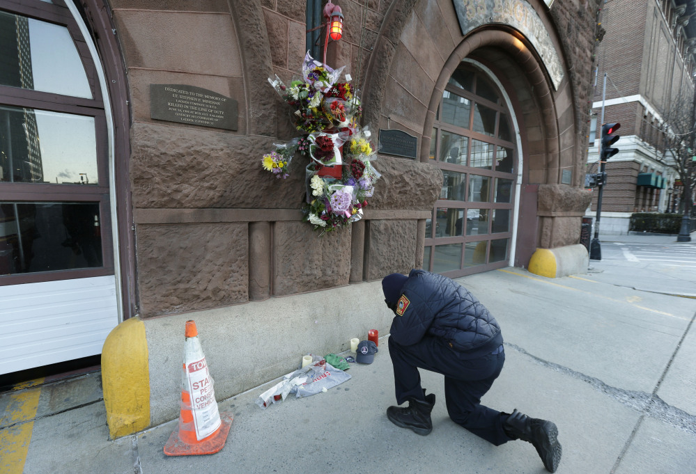 Somerville, Mass., firefighter Earl Johnson kneels to pray in front of a makeshift memorial on the front of fire station Engine 33 on Thursday in Boston. Fire station Engine 33 was the station of fallen firefighters Lt. Edward J. Walsh and Michael R. Kennedy.