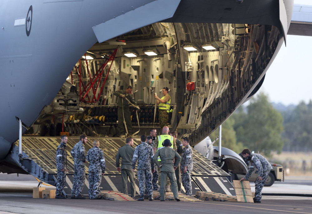 Ground crew prepare to unload a Sea Hawk helicopter from a Royal Australia Air Force C-17 after it landed at RAAF Base Pearce to help with the search for the missing Malaysia Airlines Flight MH370 in Perth, Australia, on Friday.